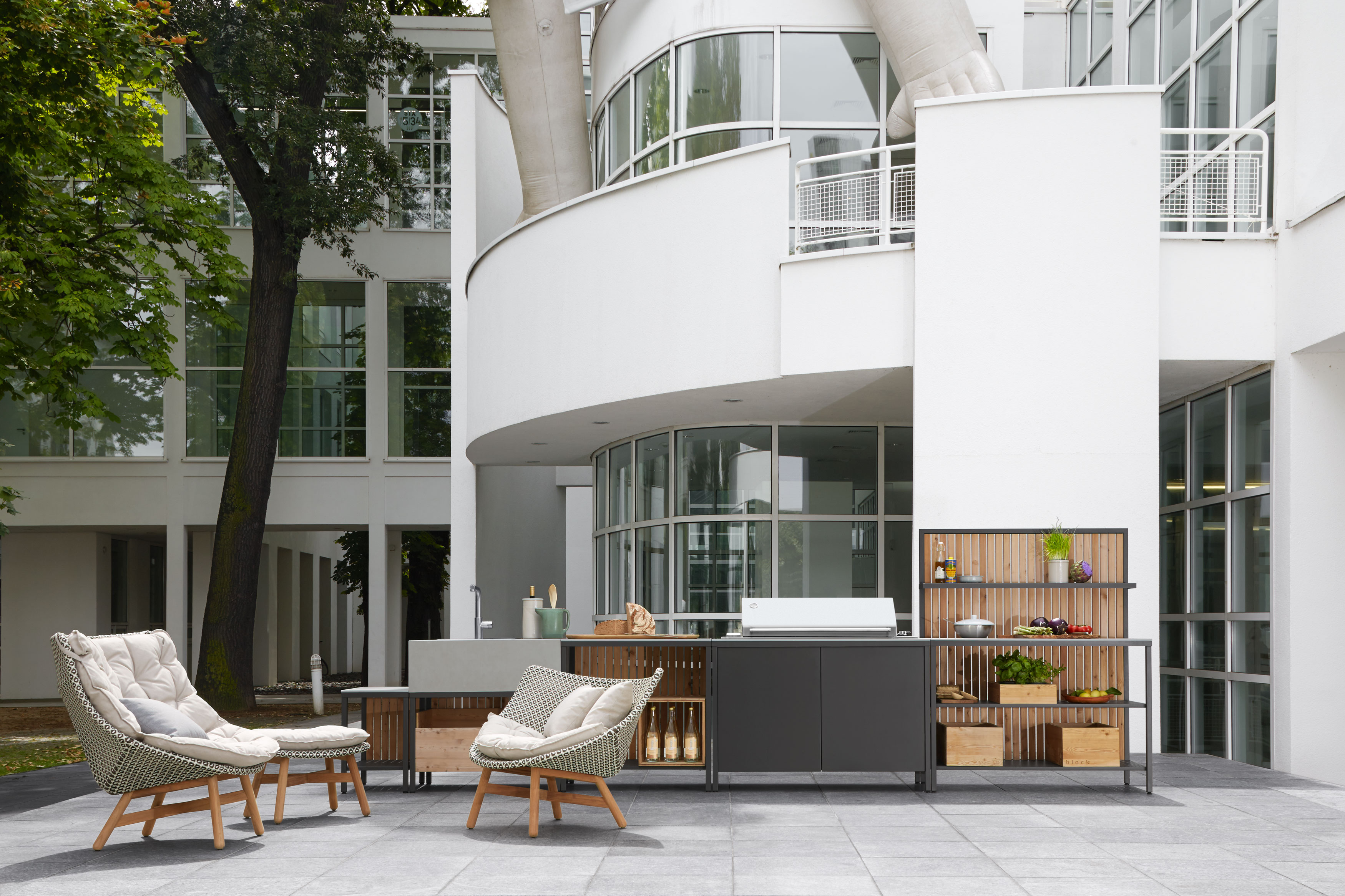 block outdoor kitchen behind dedon chairs