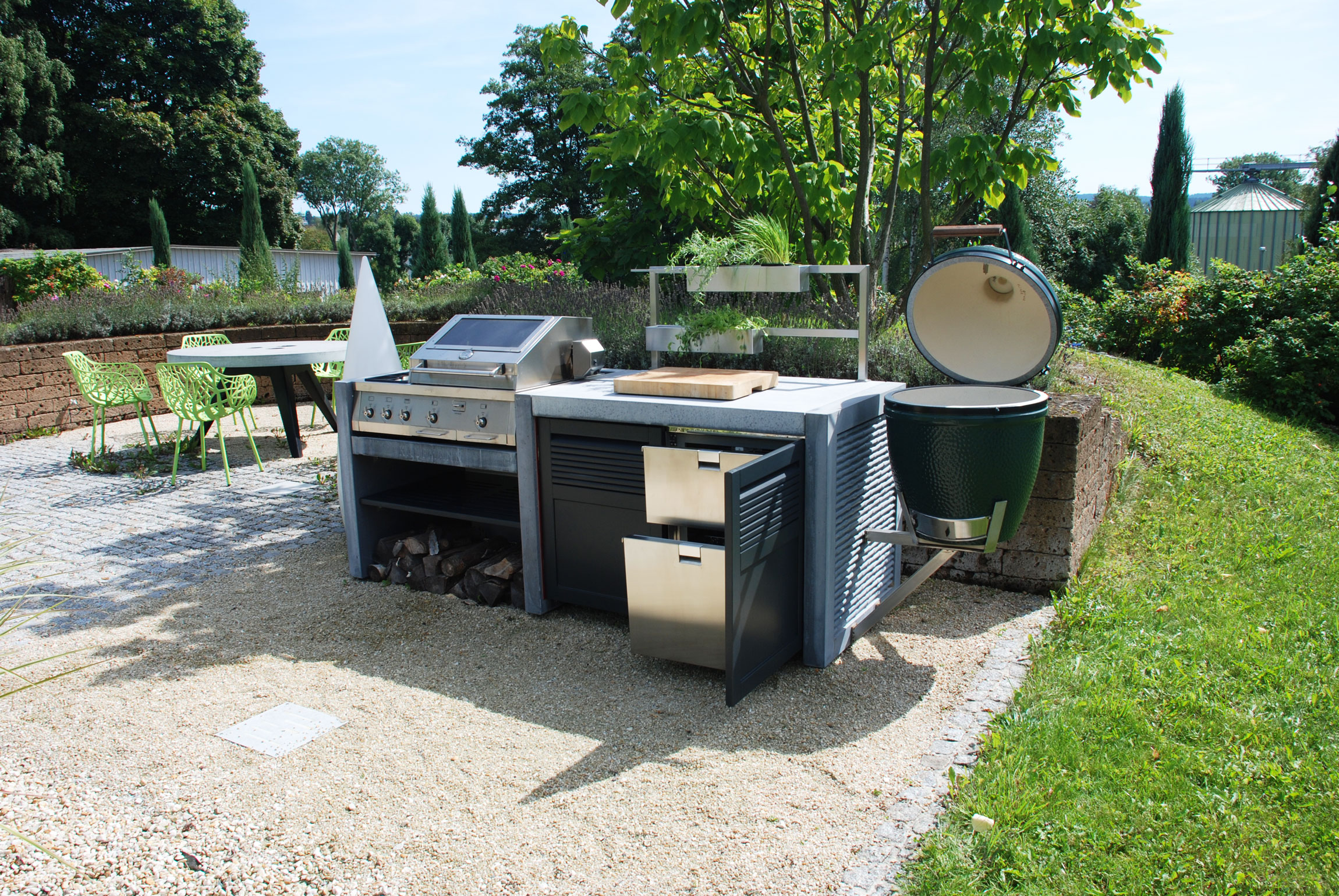 conrete outdoor kitchen with biggreenegg and fridge